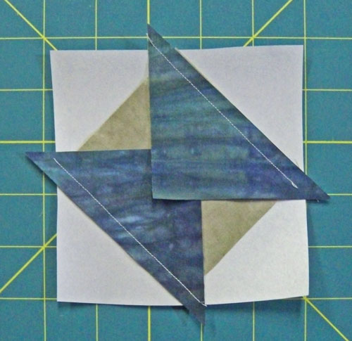Two patches of the square in a square unit are stitched before pressing