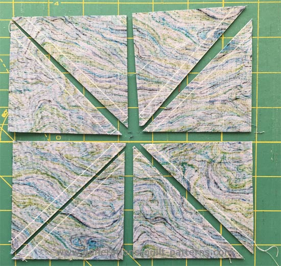 8 half square triangles ready for pressing and trimming