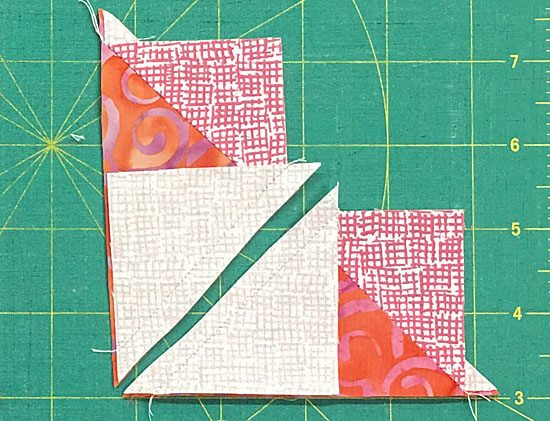 Cut the heart-shaped patches in half between the stitching