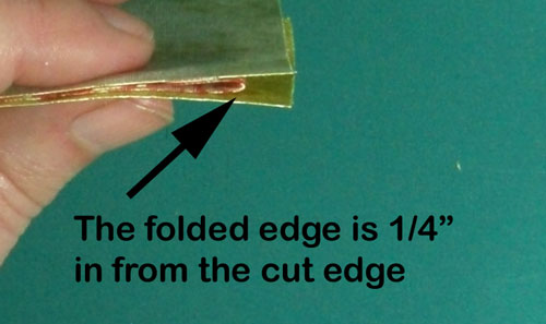 The folded edge is a quarter from the cut edge
